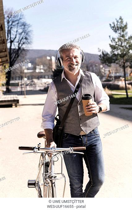 Smiling mature businessman with bicycle, takeaway coffee and headphones on the go in the city