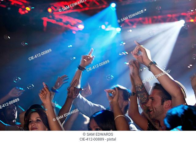 Enthusiastic crowd with arms raised on dance floor of nightclub