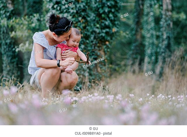 Woman crouching with baby daughter in park, Chenonceaux, Loire Valley, France