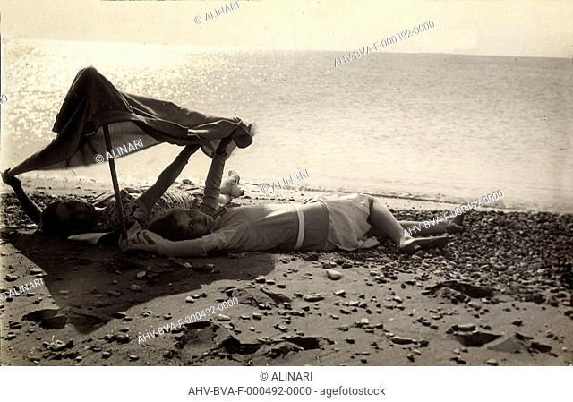 Two women lying on the sea shore in the shade of a towel. Postcard sent by the photographer to Vincenzo Balocchi, shot 1926 by Pacho', Ludovico