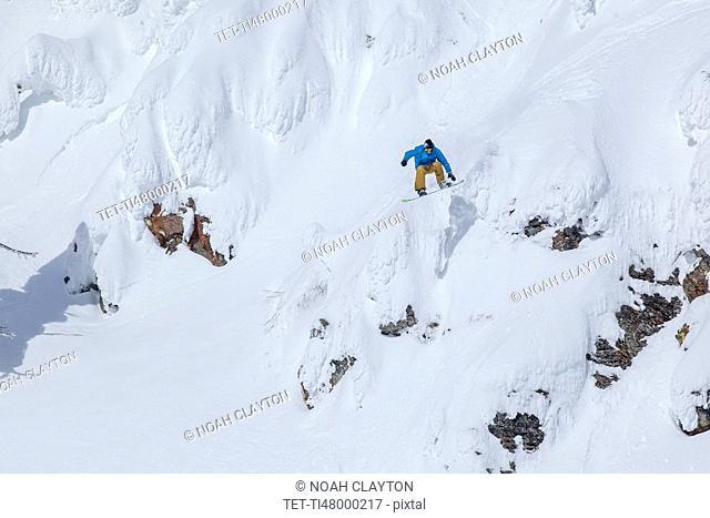 Man snowboarding down mountain