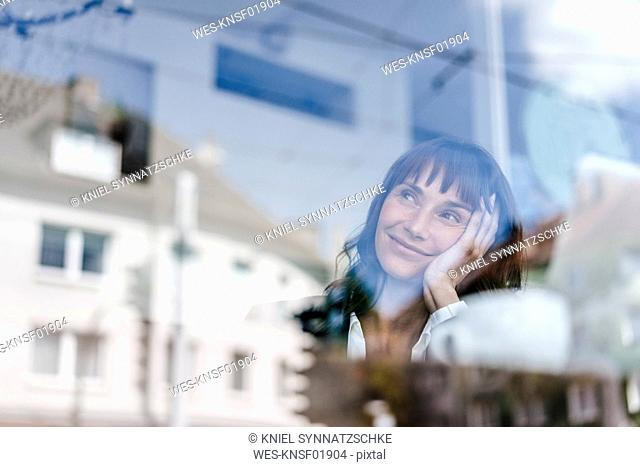Businesswoman sitting in cafe, daydreaming