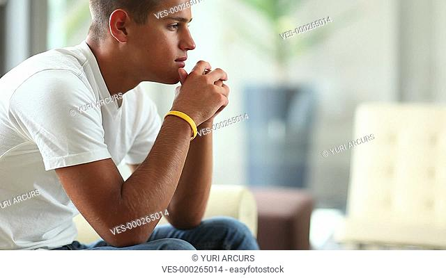 A young man looking thoughtful at home and giving you a smile - Copyspace