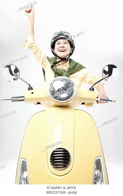 Middle aged woman in helmet driving a motorcycle with her hand up