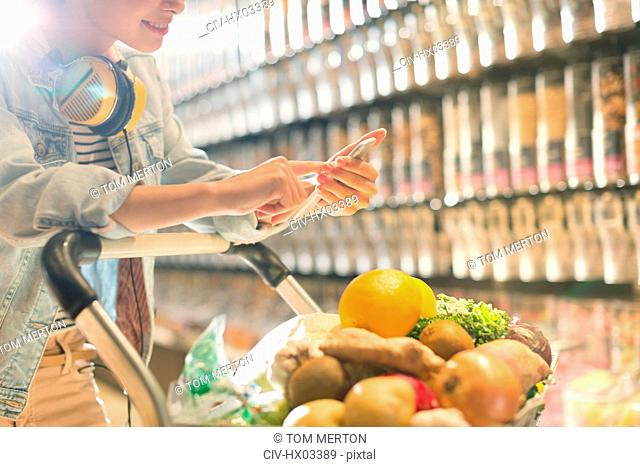 Young woman with headphones using cell phone, grocery shopping in market