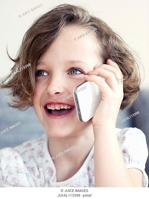 Young girl using cellphone, smiling