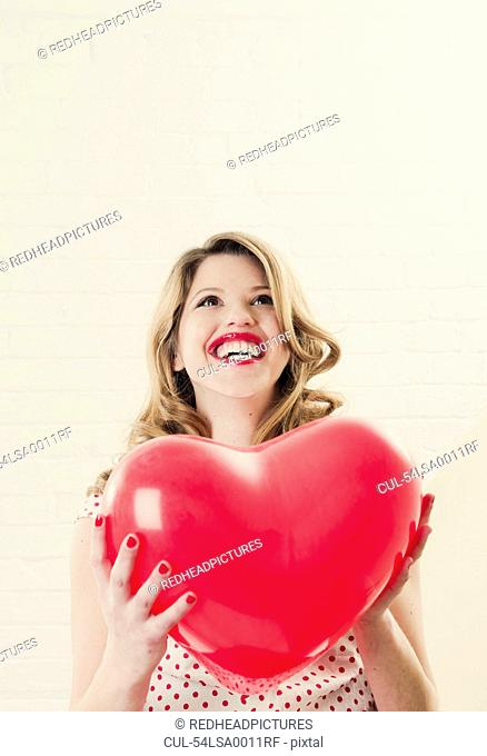 Woman holding heart shaped balloon