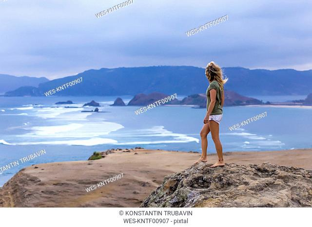 Indonesia, Lombok, woman standing at the coast looking at view