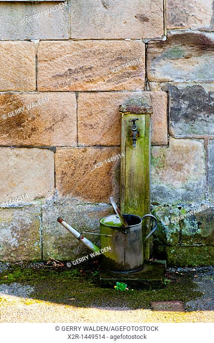 A watering can sitting under a tap in a churchyard in Derbyshire