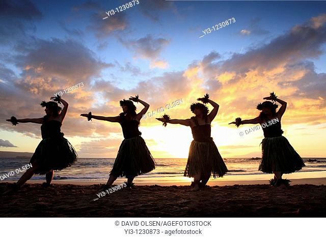 Silhouette of hula dancers at sunset at Palauea Beach, Maui, Hawaii