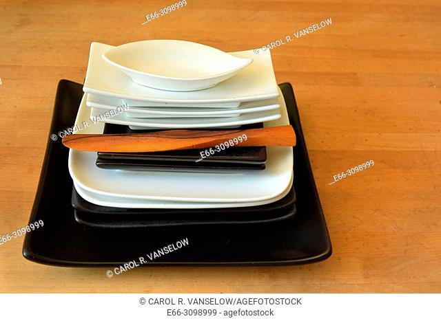 Stack of different shaped black and white plates and wooden knife. Low point of view