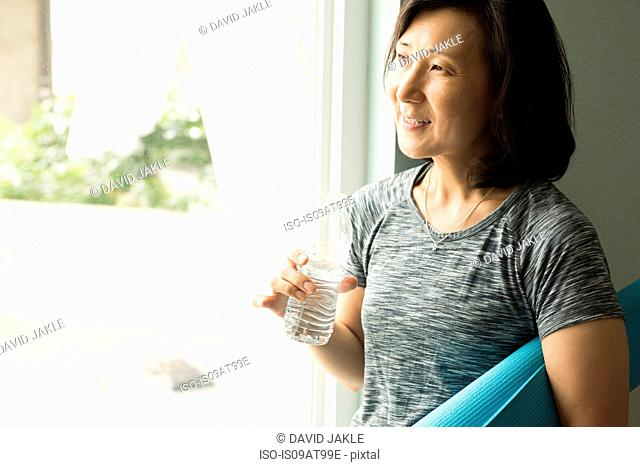 Mature woman holding rolled up yoga mat and bottle of water looking out of window smiling