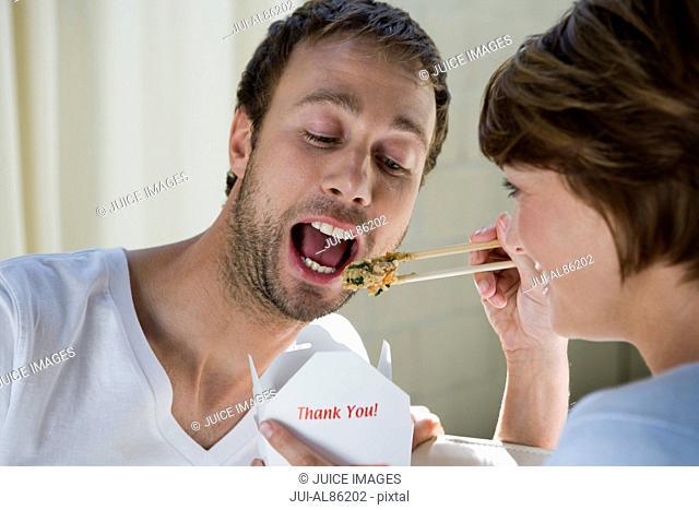 Woman feeding boyfriend with chopsticks