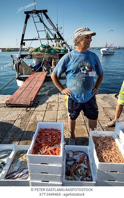 Fishermen selling the days catch on the quay in the old town of Gallipoli, Puglia, Southern Italy
