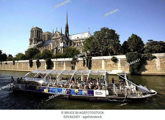 Notre-Dame Cathedral with a tour boat in River Seine in foreground. Paris. France