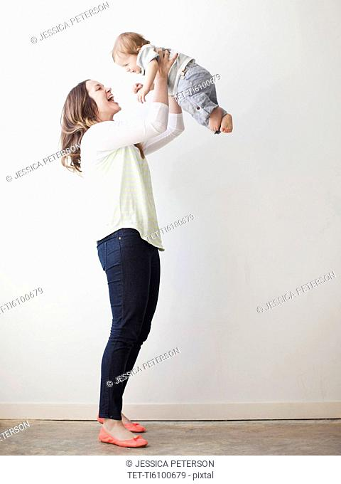 Young mother lifting baby boy 6-11 months mid-air