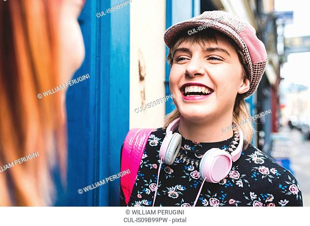 Stylish young woman in baker boy hat laughing with friend on city street