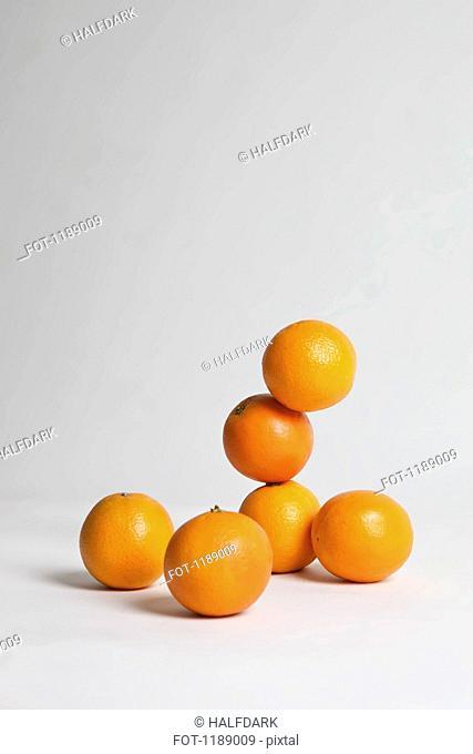 Oranges stacked precariously, studio shot
