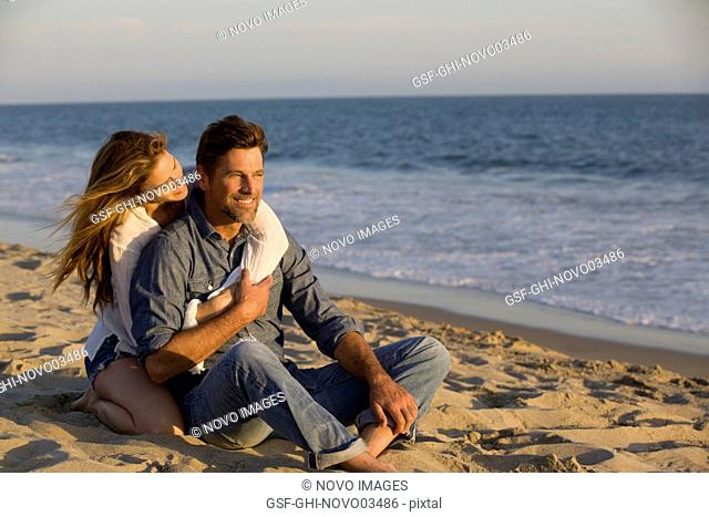 Affectionate Mid-Adult Couple Sitting on Sandy Beach