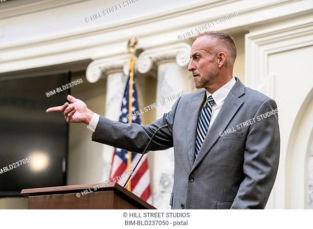 Caucasian politician at podium pointing