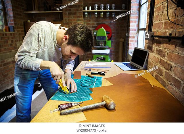 A craftsman using a rotary cutter wheel on a cutting mat on a small piece of brown leather