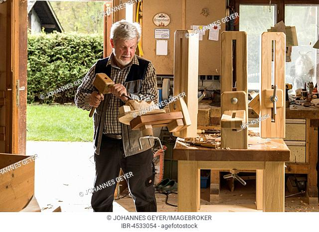 Wooden mask carver using wood carving tools at workbench in workshop, Bad Aussee, Styria, Austria