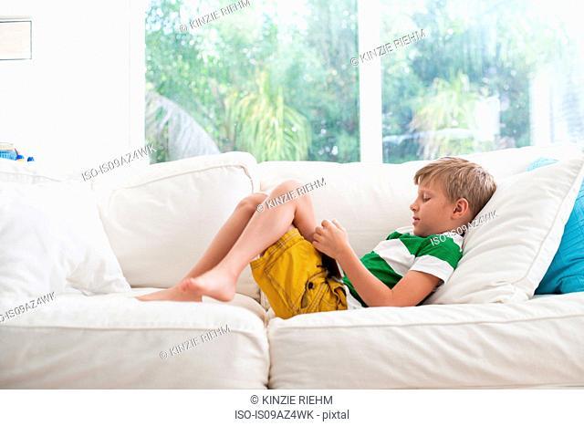 Boy lying on sofa using digital tablet