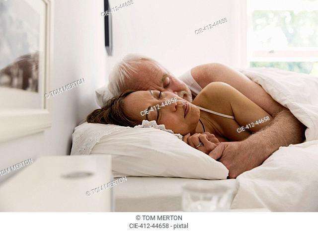 Serene senior couple sleeping in bed