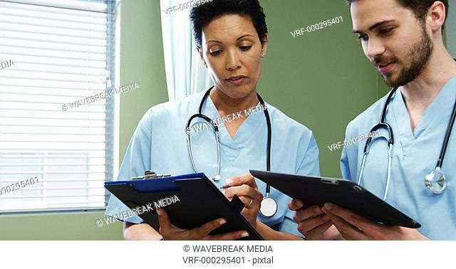 Two doctors discussing over digital tablet