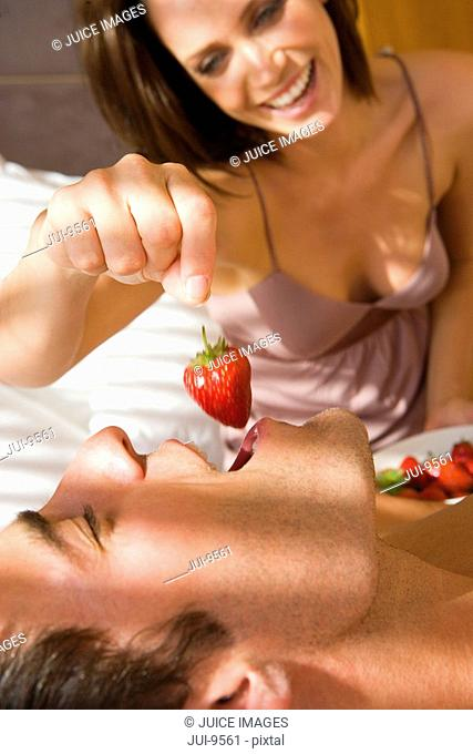 Young woman holding strawberry above man's mouth in bedroom