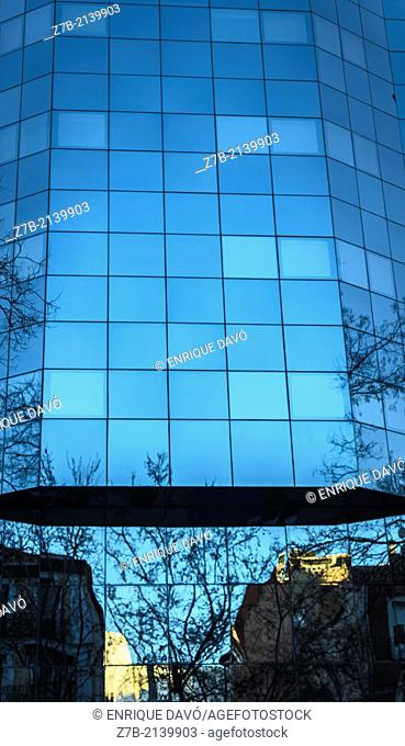 A houses reflect on a blue building in a central street of Madrid city, Spain