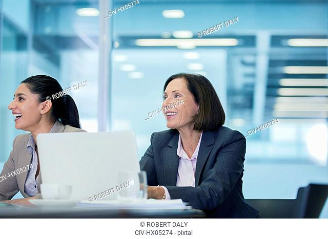 Smiling businesswomen listening in conference room meeting