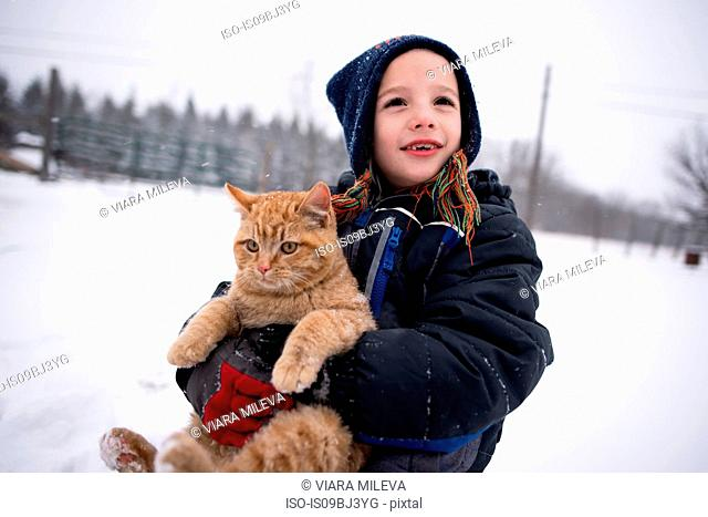 Boy carrying cat in snow