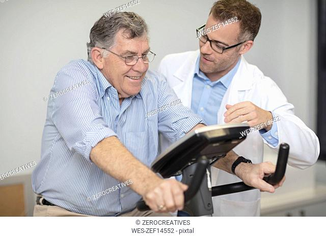Doctor looking at senior patient on exercise machine