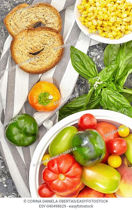 Healthy ingredients mix with various types of tomatoes, bell peppers, corn, basil and apulian bread called frisella