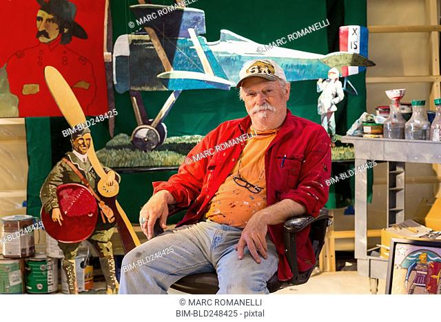 Portrait of older Caucasian man sitting in workshop