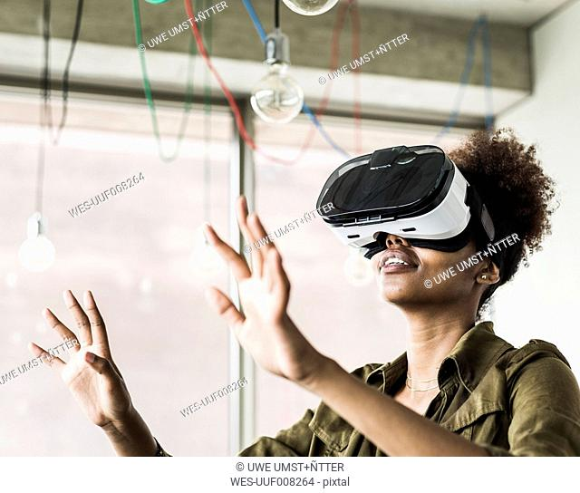 Woman in office using virtual reality glasses