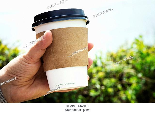 Close up of a human hand holding a disposable paper cup with a cardboard sleeve and plastic lid