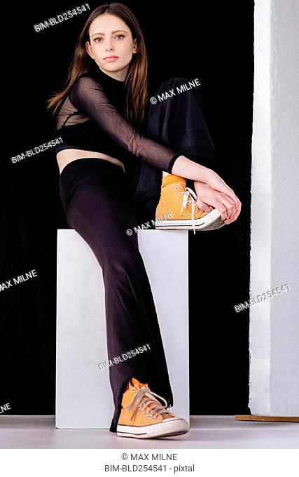 Serious Caucasian woman sitting on pedestal