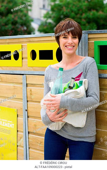 Woman taking recyclables to recycling bin