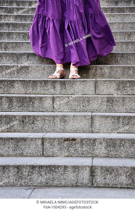 Young woman wearing purple dress standing on steps