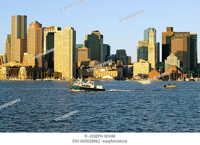 Boat travels in front of Boston Harbor and the Boston skyline at sunrise as seen from South Boston, Massachusetts, New England