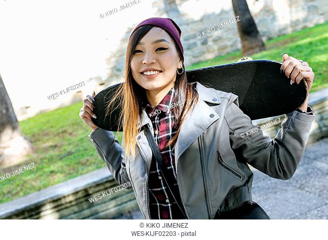 Portrait of smiling young woman with skateboard on her shoulders