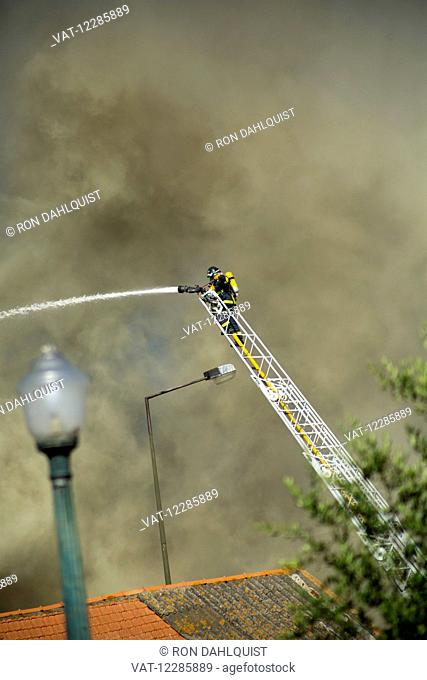 Firefighter spraying water on building fire; Lisbon, Portugal