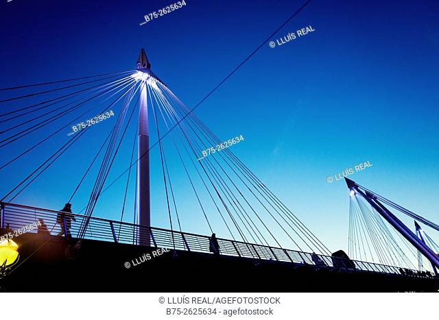 View of the Golden Jubilee Bridges in the evening with a silhouette of unrecognizable people walking through the bridge. River Thames, London, England