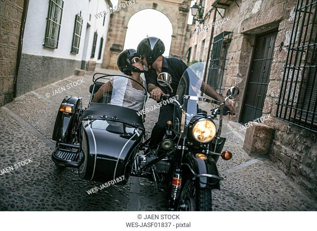 Spain, Jaen, mature couple on motorcycle with a sidecar kissing on an alley
