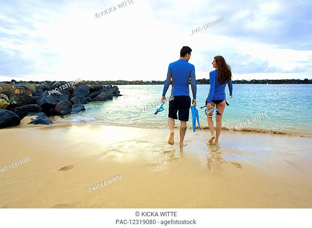 A couple walks into the water from Lydgate Beach holding flippers and snorkeling gear; Kauai, Hawaii, United States of America