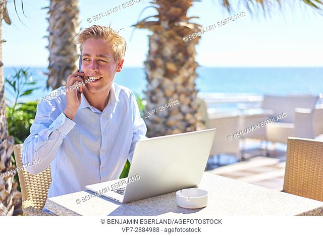 business man using mobile phone and laptop at holiday location. Dutch ethnicity. In Hersonissos, Crete, Greek