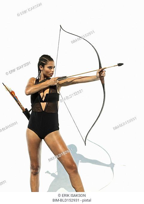 Mixed race woman aiming bow and arrow