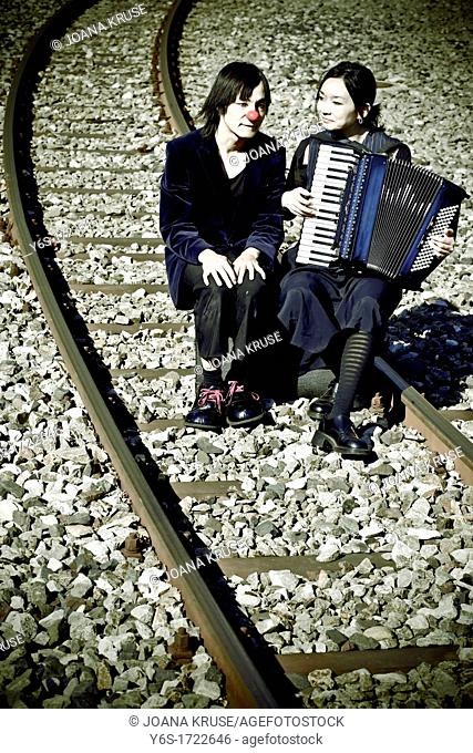 a clown couple sitting on railroad tracks, the woman plays music